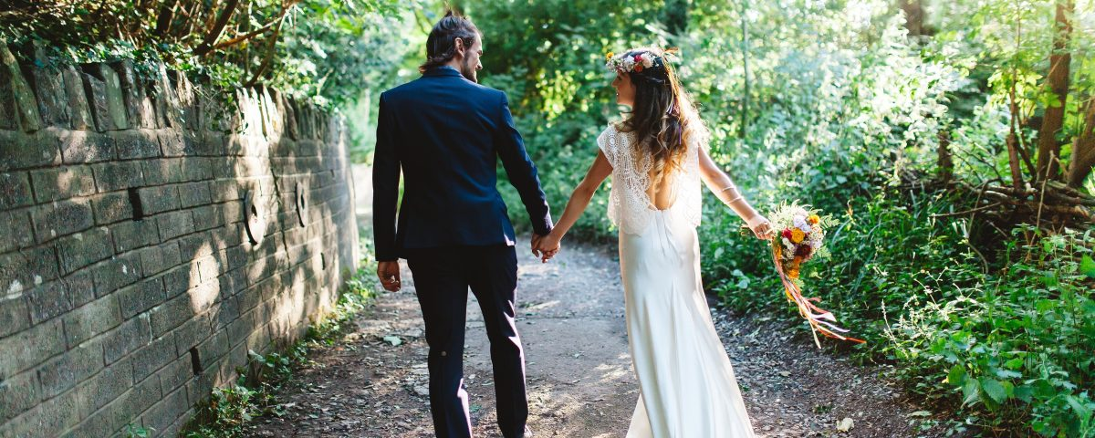 bride and groom walking hand in hand up woodland path holding flower bouquet