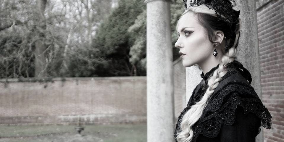 Goth woman standing in profile with victorian mourning clothes on outside