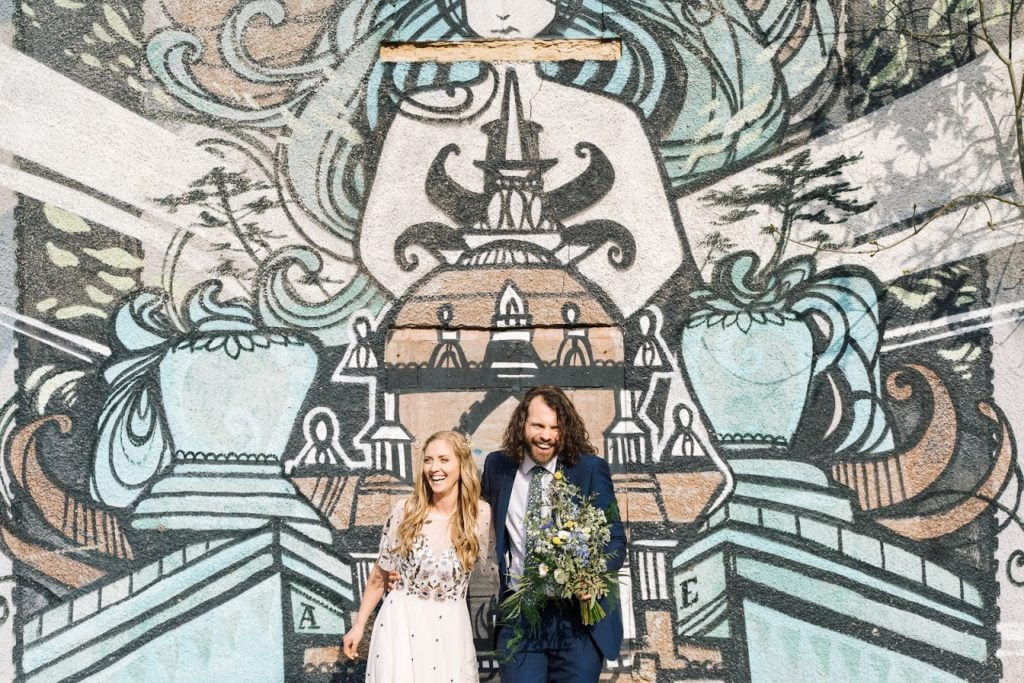 Wedding couple in front of graffiti wall