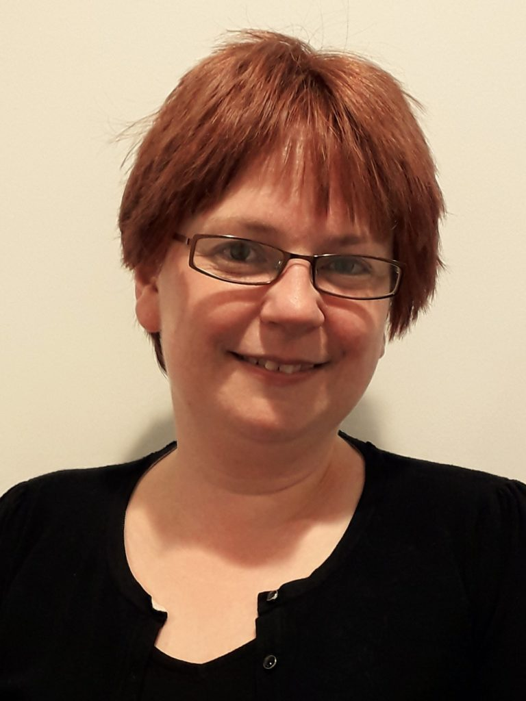 Academic Woman with red bob wearing glasses name Dr Helen Frisby