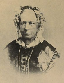 Mary Carpenter as an older white Victorian lady with bonnet and ringlets