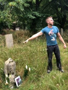 A white man in grass with blue t-shirt pointing at a grave